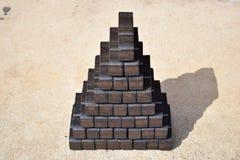 Kolbrikett, kvarter för kolbrikett, kvarter för kolbrikett, hög av kolbriketter, kvarter för styckkolbriketter, svart briquett Arkivbilder