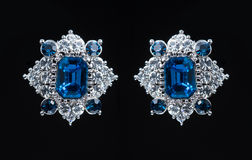 Kolczyk z kolorowymi błękitnymi klejnotami na czerni obrazy royalty free