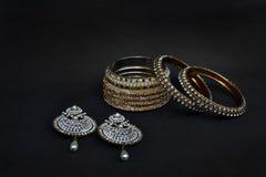 Kolczyki i bangles z srebrem i złotem pokrywającymi Obraz Stock