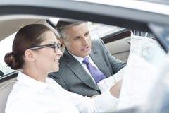 Koledzy dyskutuje nad mapą w samochodzie obrazy royalty free