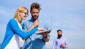 Koledzy dyskutuje plan z laptopem Kolegi laptopu pracy plenerowy słoneczny dzień, nieba tło Świeże powietrze pomoce zdjęcia stock