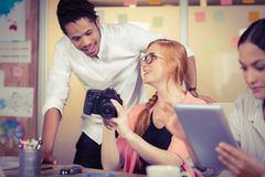 Koledzy trzyma kamerę z bizneswomanem używa cyfrową pastylkę w przedpolu Zdjęcia Stock