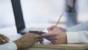 Kolegów dyskutować raportowy i robić obliczeniu na smartphone, bierze notatki zdjęcie wideo