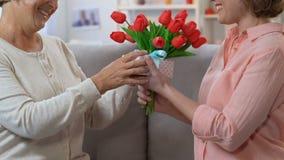 Kolega daje teraźniejszość przyjaciel na Międzynarodowych kobietach dzień, wiosna wakacje zbiory