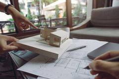 Kolega drużyna architekci dyskutuje i wskazuje przy architektura modelem z sklepowym rysunkowym papierem i laptopem fotografia stock