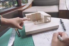 Kolega drużyna architekci dyskutuje i wskazuje przy masa modelem z sklepowym rysunkowym papierem i laptopem Zdjęcie Stock