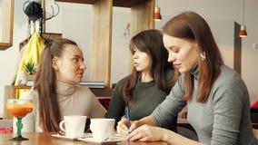 Kolega kobiety dyskutują wspólnego projekt w kawiarni w coworking centrum i robią notatki w notatniku obraz royalty free