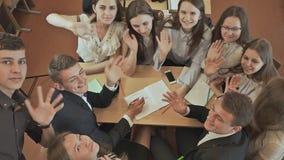 Kolega z klasy siedzą wokoło biurka, dyskutują szkolnego zadanie i wtedy machają ich ręki Rosjanin szkoła zbiory