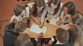 Kolega z klasy siedzą wokoło biurka i dyskutują szkolnego zadanie Rosjanin szkoła zbiory wideo