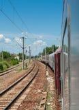 Kolej i pociąg iść horyzont w zieleń krajobrazie pod niebieskim niebem z białymi chmurami Obrazy Stock