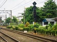 Kolej z elektrycznym kablem dla dojeżdżający linii otaczania drzewami i krzaki przy Depok Stacjonujemy fotografię brać w Depok Fotografia Stock
