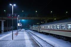 Kolejowa platforma z pociągiem przy nocą w zimie Obrazy Royalty Free