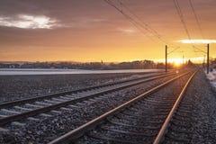 Kolejowi ślada przez zamarzniętej natury przy wschód słońca Podróżny kontekst Zima wakacje podróż obraz royalty free