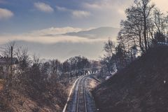 Kolejowy ślad wśród drzewo linii i zimy pasma górskiego Obrazy Stock