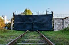 Kolejowych śladów bieg w czarną bramę strefa przemysłowa zdjęcie stock