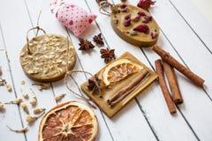 Kolekcja handmade mydło z wysuszonymi kwiatami wzrastał, pomarańcze, owies, cynamonowi kije na białym drewnianym tle obraz stock