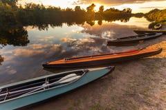 Kolekcja kolorowi kajaki na brzeg rzeki przy letnim dniem Fotografia Stock