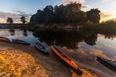 Kolekcja kolorowi kajaki na brzeg rzeki przy letnim dniem Obraz Royalty Free