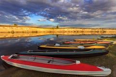 Kolekcja kolorowi kajaki na brzeg rzeki przy letnim dniem Zdjęcie Stock
