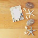 Kolekcja nautyczni i plażowi przedmioty tworzy ramę nad drewnianym tłem, Zdjęcia Royalty Free