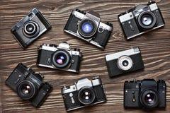 Kolekcja retro SLR kamery na drewnianym tle fotografia royalty free