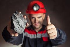 Kolgruvarbetaren med klumpa sig av kol arkivfoto