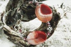 Kolia z agatów gemstones na miękkim piaska tle Obrazy Stock