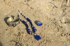 _ Kolii bransoletka na piasku na unny dniu i pierścionek Obrazy Royalty Free