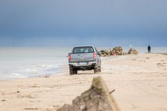KOLKA LETTLAND - 26 OKTOBER 2018: Den Fiat backen väljer upp lastbilen som kör i stranden arkivbild
