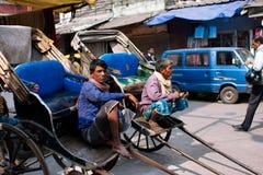 KOLKATA, ИНДИЯ: Пожилые работники рук-вытягиванной рикши сидят внешнее и ожидание для пассажиров Стоковые Фото