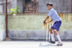 KOLKATA, INDIA – APRIL 14, 2013: Poor indian boy ready to make a beat in cricket game. KOLKATA, INDIA – APRIL 14, 2013: Poor indian boy concentrate on a bal Stock Photo