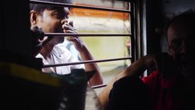 Traveling on train in india. Kolkata, India - December 2016, view through train window portrait indian man looking into train window train stop on the platform stock video footage