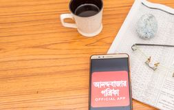 Kolkata, India, February 3, 2019: Anandabazar Patrika Bengali news app visible on mobile phone screen and placed over a wooden stock images