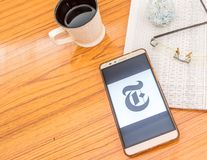 Kolkata, India, February 3, 2019: The New York Times news app visible on mobile phone screen beautifully placed over a wooden. Table with a newspaper and a cup royalty free stock photos