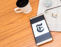 Kolkata, India, February 3, 2019: The New York Times news app visible on mobile phone screen beautifully placed over a wooden. Table with a newspaper and a cup stock photos