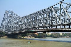 KOLKATA, INDIA Howrah Bridge. KOLKATA, INDIA - MARCH 13: Fisherman boat crosses the Hooghly River nearby the Howrah Bridge on March 13, 2013. Hooghly Bridge is a Stock Photography
