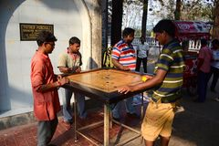 Indian men playing carrom game. Kolkata, India - March, 2014: Indian men playing carrom game - traditional tabletop game. Young adults have fun on street Royalty Free Stock Photo