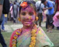 A young little girl smeared with colours in the festival of holi in India stock photos
