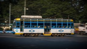 A panning shot of a Tram with passengers in Kolkata, West Bengal, India stock image