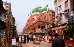 KOLKATA INDIEN: Folket flyttar sig på den upptagna gatan förbi den Nakhoda Masjid moskén royaltyfri foto