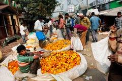 KOLKATA INDIEN: Indiska affärsmän säljer de stora korgarna av blommorna i marknad Royaltyfri Fotografi