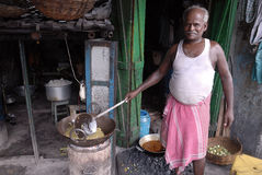 Kolkata's Slum Area. SUKHE RAM 58 years old making food for his roadside hotel at Park circus slum area in Kolkata.Once he was a child labour at Kolkata's food Royalty Free Stock Photography