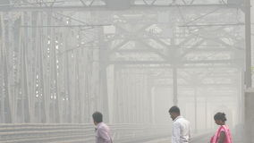 Kolkata Train Bridge People 4k. People cross railway before the approaching train on the bridge over the Hooghly river in foggy atmosphere in Kolkata, India stock footage