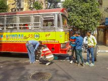 Tyre puncture on a busy road. Kolkata, West Bengal, India- December 17, 2017: A bus tyre puncture was held on a busy road and then a group of labor try to Royalty Free Stock Image