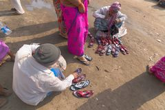 Seller selling shoes to sari clad Indian women, Kolkata, India. KOLKATA, WEST BENGAL , INDIA - JANUARY 18TH 2015 : A seated Indian male selling colorful chappals Royalty Free Stock Photo