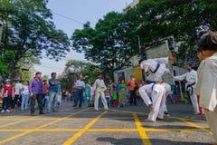 KOLKATA, WEST-BENGALEN, INDIA - MAART EENENTWINTIGSTE 2015: De jonge jongen in witte gesprongen kleding ging twee medejongens ove stock fotografie