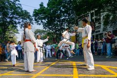 KOLKATA, WEST-BENGALEN, INDIA - MAART EENENTWINTIGSTE 2015: Jonge jongen die in witte kleding van grond aan schop, karatepraktijk stock afbeeldingen