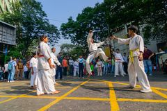 KOLKATA, WEST-BENGALEN, INDIA - MAART EENENTWINTIGSTE 2015: Jonge jongen die in witte kleding van grond aan schop, karatepraktijk royalty-vrije stock foto's