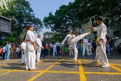 KOLKATA, WEST-BENGALEN, INDIA - MAART EENENTWINTIGSTE 2015: Jonge jongen die in witte kleding van grond aan schop, karatepraktijk stock afbeelding