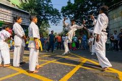 KOLKATA, WEST-BENGALEN, INDIA - MAART EENENTWINTIGSTE 2015: Jonge jongen die in witte kleding van grond aan schop, karatepraktijk royalty-vrije stock afbeelding
